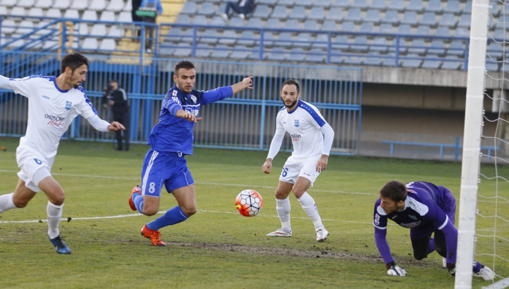 Ejupi (in blue) lunges at the ball