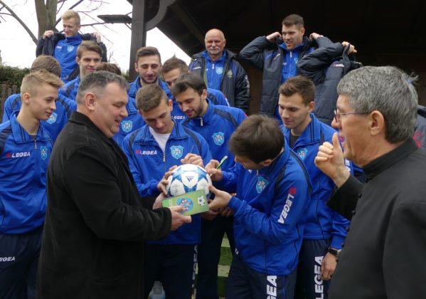 Nogometaši Koprivnice potpisuju nogometnu loptu za močilskog župnika // Foto: NK Koprivnica